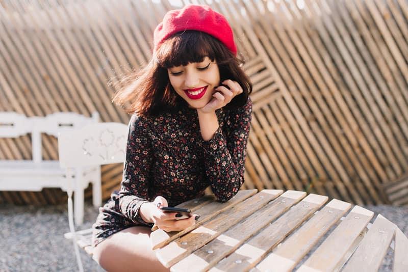 femme avec chapeau et rouge à lèvres en regardant le téléphone