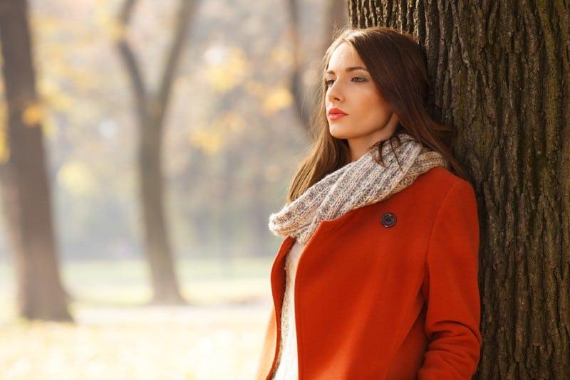 Portrait d'une belle femme brune en automne parc s'appuyant sur un arbre