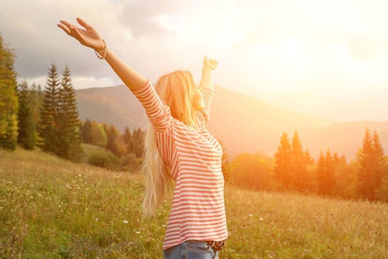 femme heureuse, écartant les bras en plein air