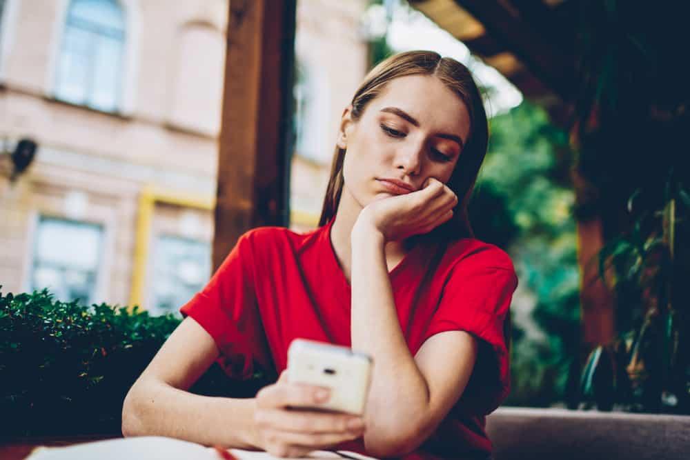 femme triste au bouton de la table sur le téléphone