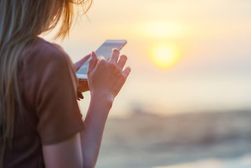 fille tapant sur un téléphone portable au coucher du soleil