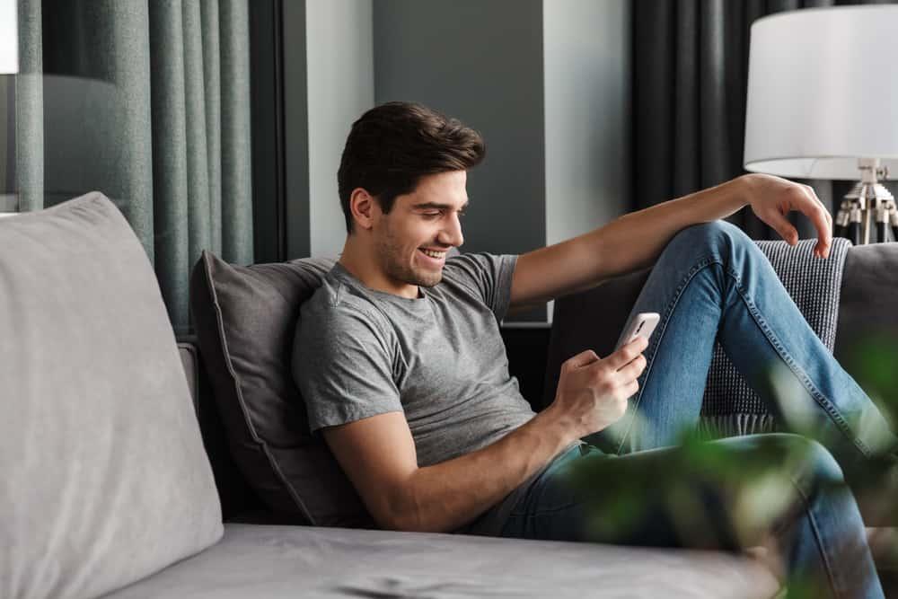 homme namijani est assis sur le canapé et écrit des sms