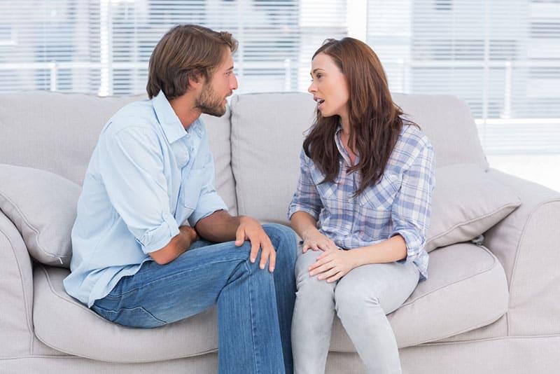 jeune couple parlant sur le canapé