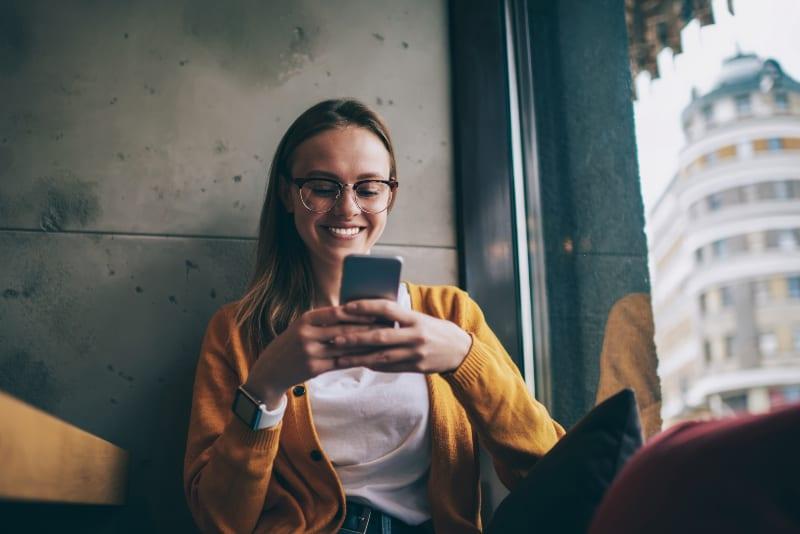 jeune fille avec bouton de lunettes sur téléphone portable
