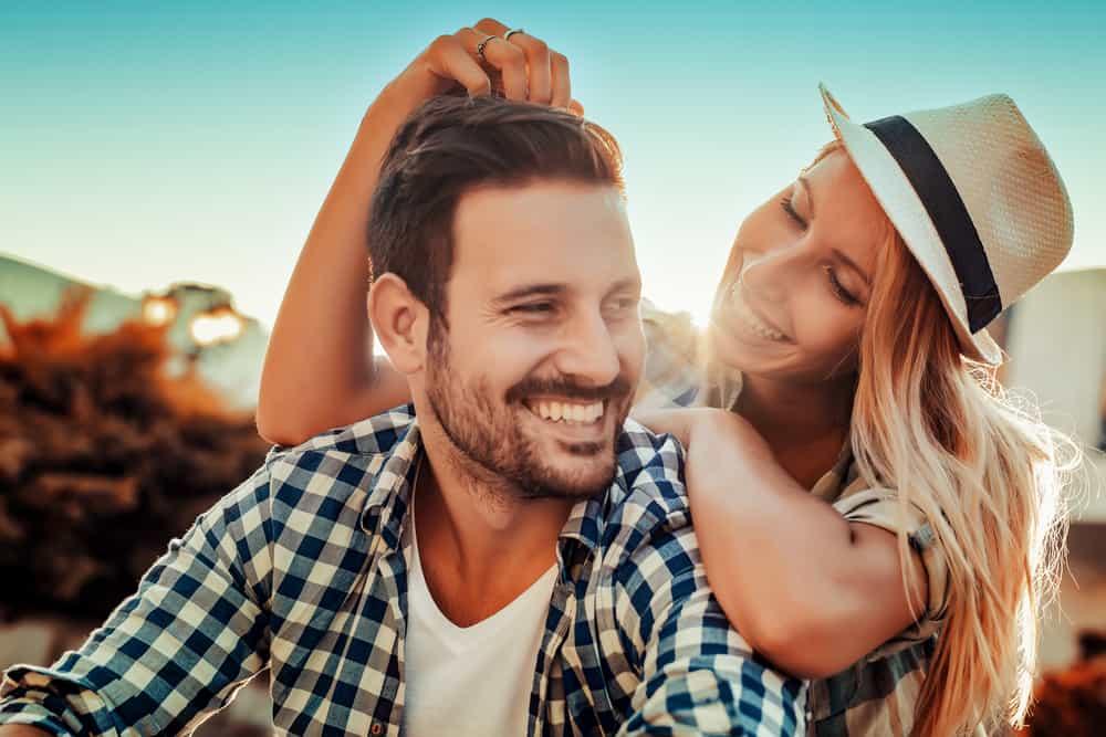 la femme au chapeau touche la tête de l'homme et rit