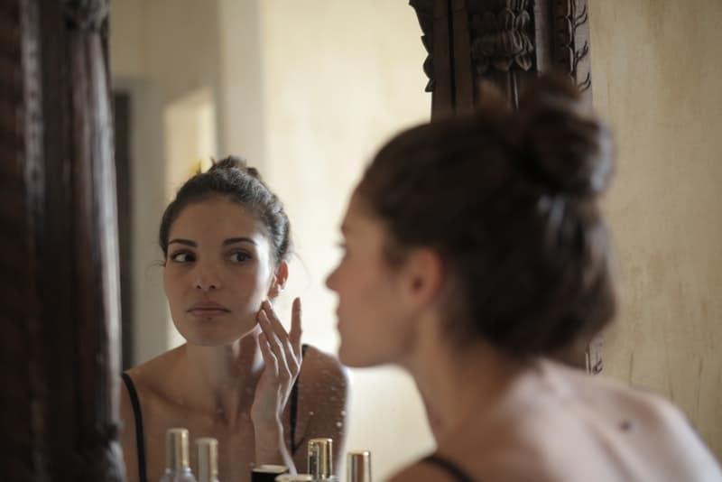 la femme devant le miroir regarde son visage