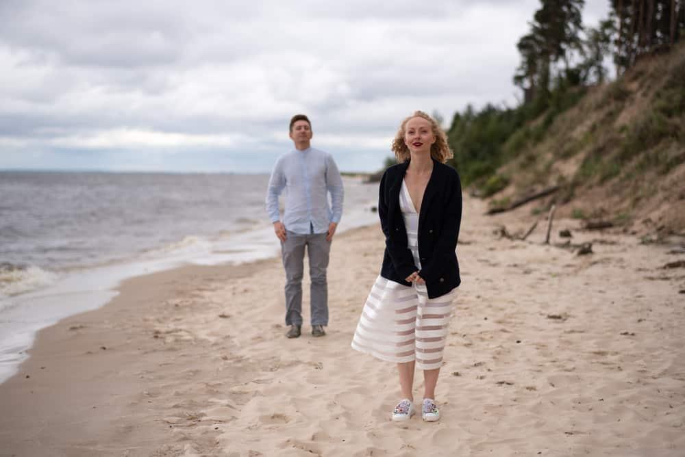 la femme marche seule sur la plage laissant l'homme