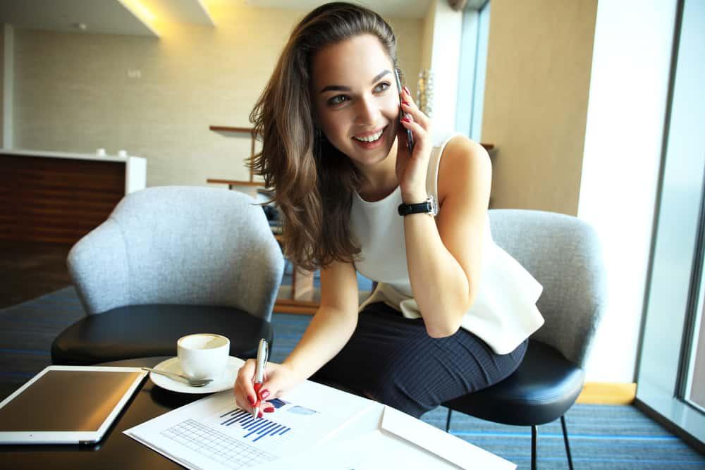 la femme parle au téléphone tout en travaillant et en riant
