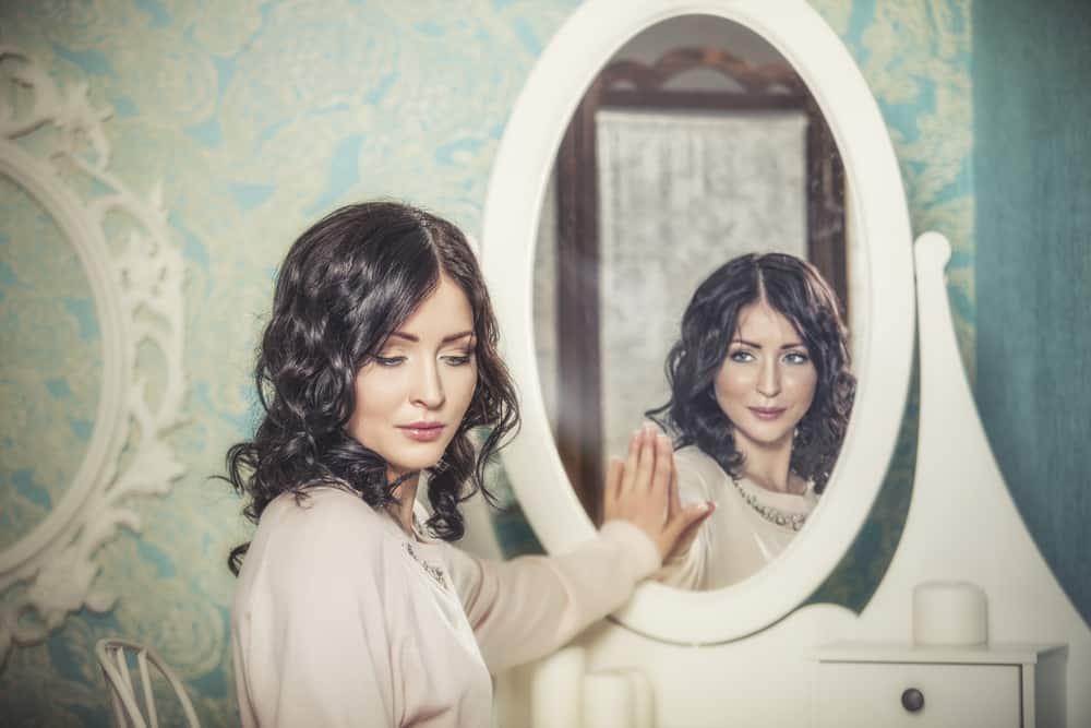 la femme posa sa main sur le miroir et se regarda