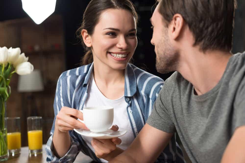 la femme rit avec du café à la main et regarde l'homme