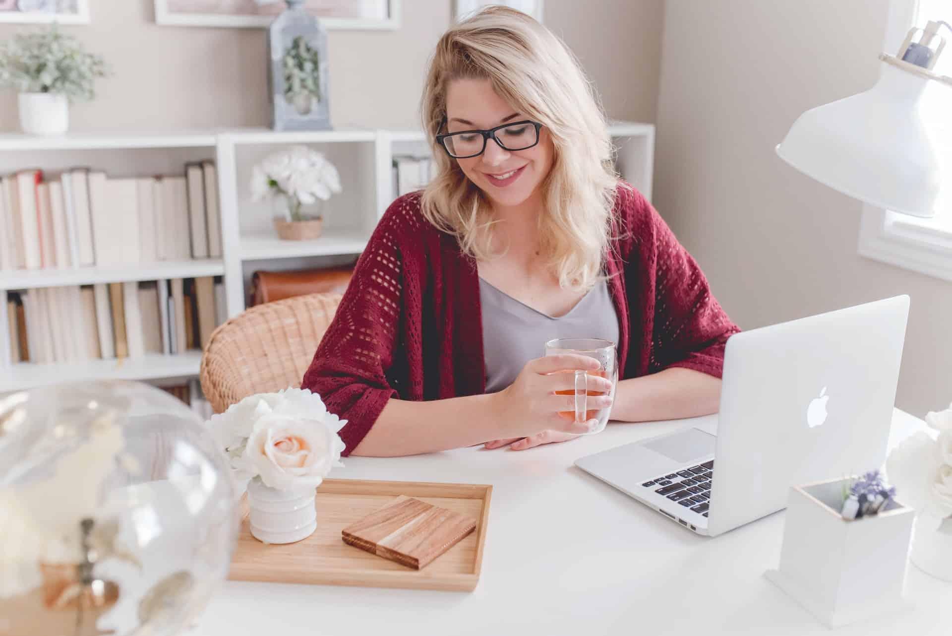 la femme s'assoit et travaille derrière l'ordinateur portable et sourit