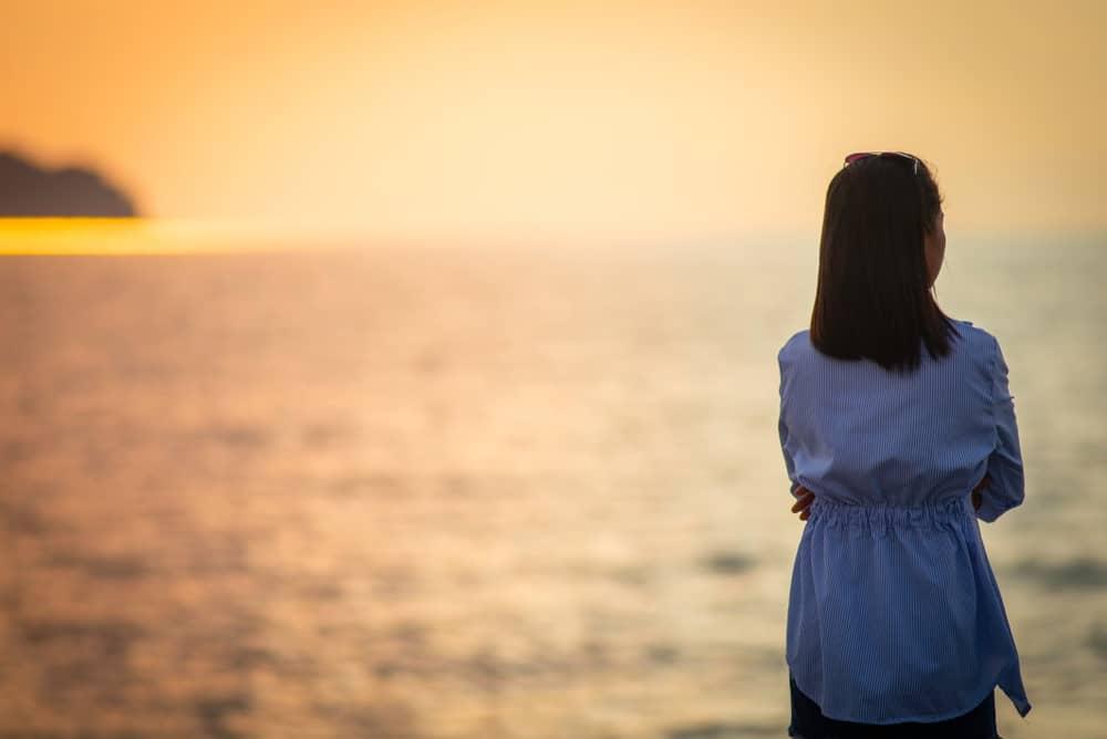 la femme se tient au bord de la mer, le dos tourné et regarde