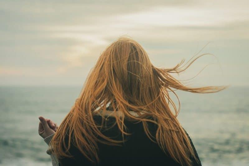 la femme se tient dos à la mer