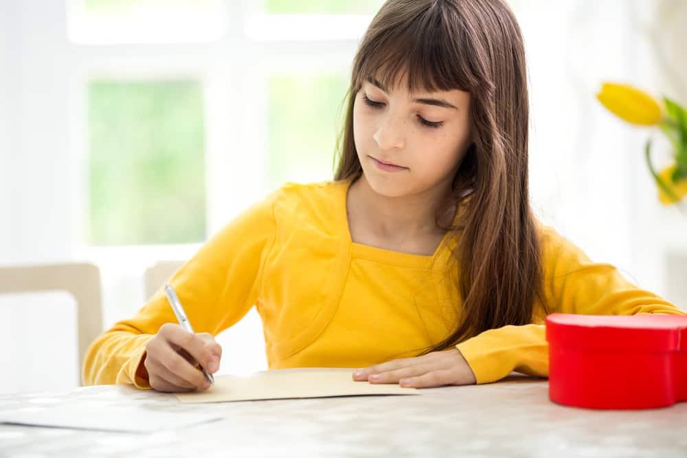 la fille à la table s'assied et écrit une carte de voeux