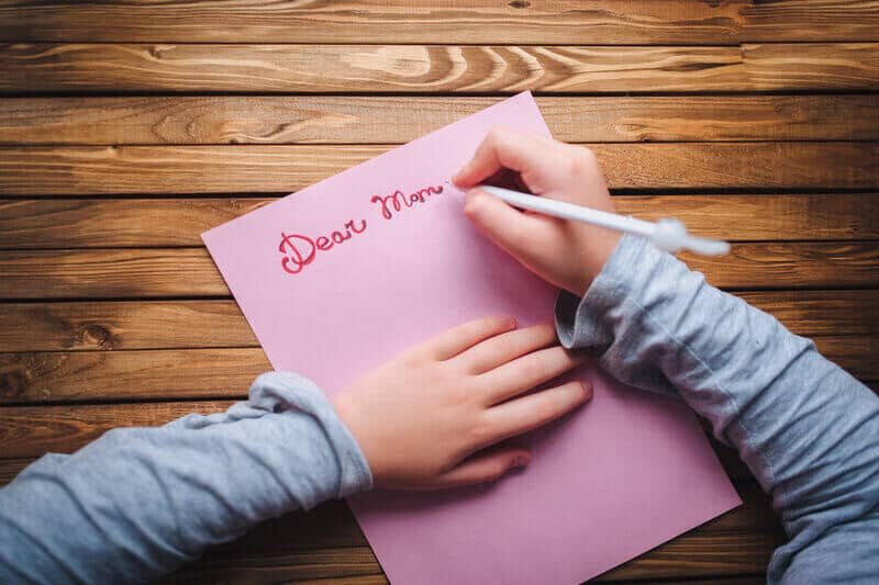 la fille écrit une carte de voeux