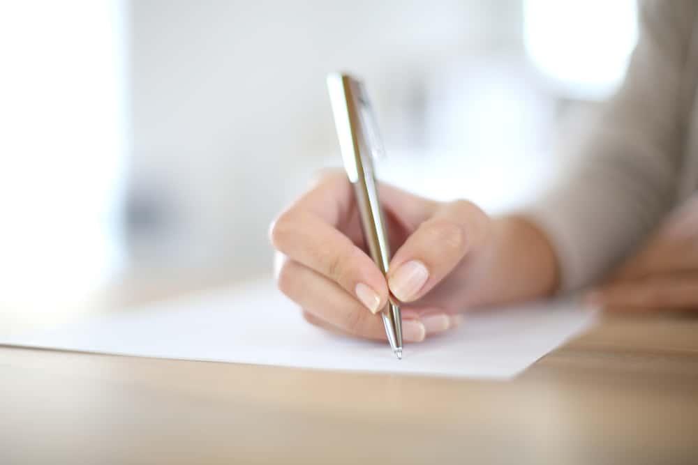 la main d'une femme écrit quelque chose sur du papier