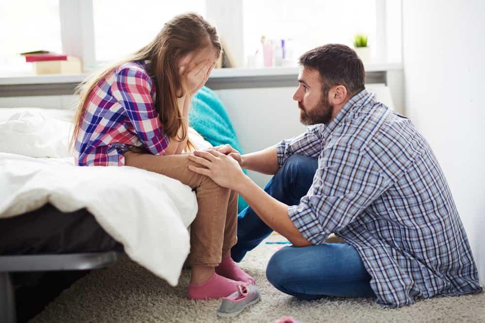le père réconforte la fille qui pleure