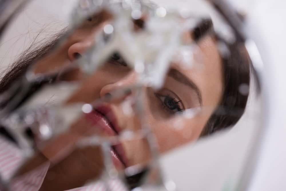 le reflet d'une femme sur un miroir brisé