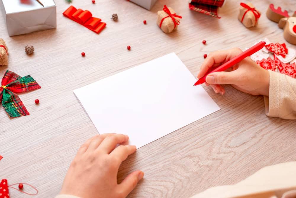 l'enfant à table écrit une carte de voeux