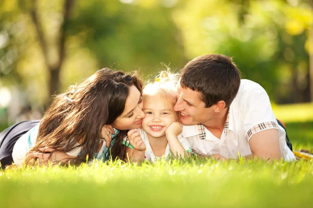 les jeunes parents s'allongent sur l'herbe dans le parc avec leur petite fille et l'embrassent