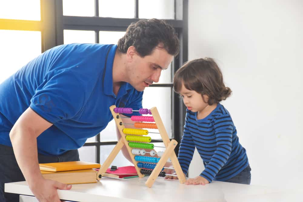 l'homme apprend à un enfant à utiliser l'abaque