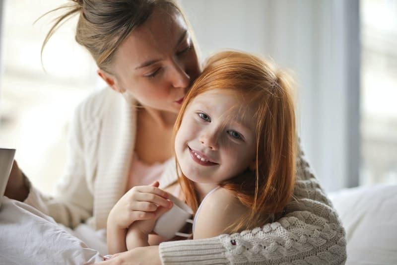 maman embrasse sa fille rousse sur la tête