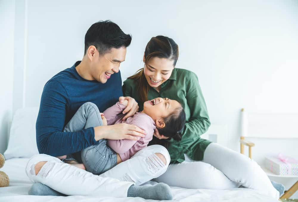 parents souriants s'amusant avec leur petite fille