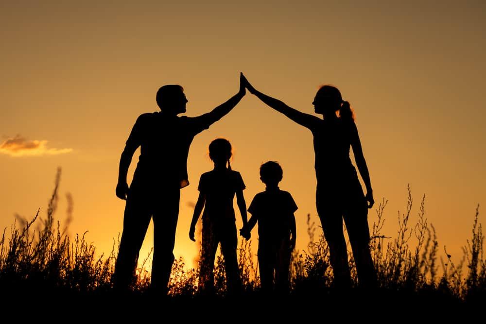 silhouette d'une famille de quatre personnes au coucher du soleil