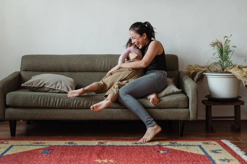 sur le canapé, l'enfant joue avec la mère