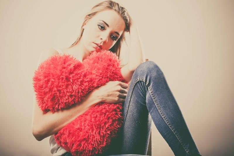 Gros plan d'une triste malheureuse femme étreignant oreiller coeur rouge