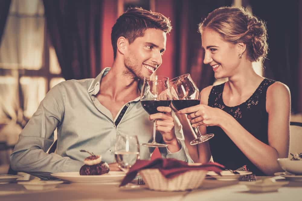 un beau couple aimant assis et grillé avec du vin dans un restaurant