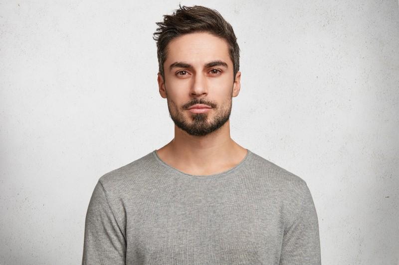 un bel homme dans un t-shirt gris