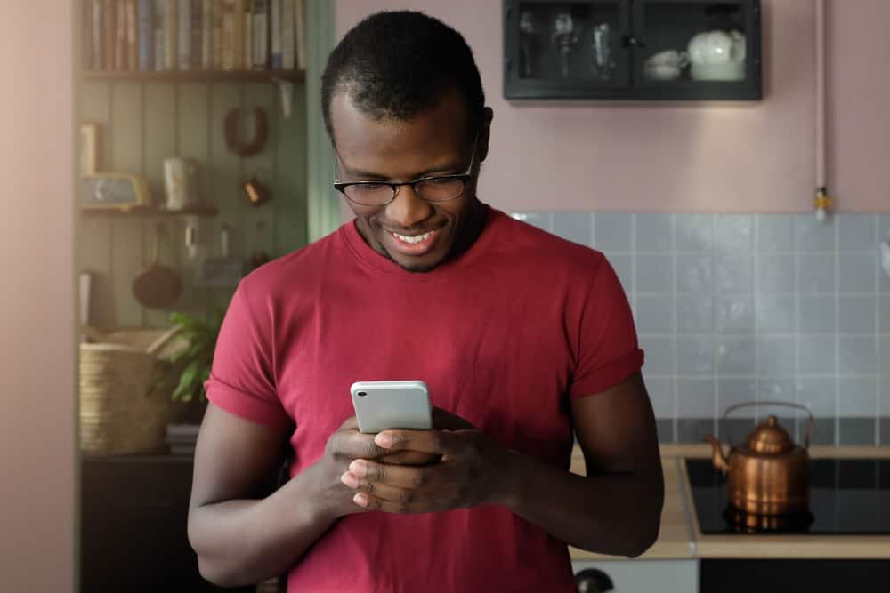 un bel homme noir est debout dans la cuisine et envoie des SMS