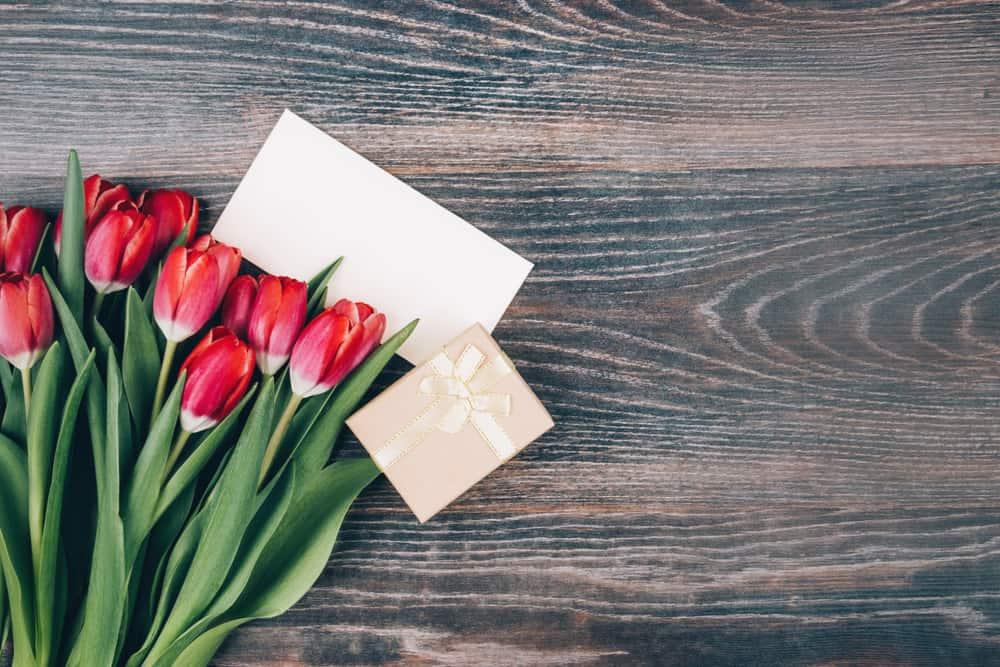 un bouquet de tulipes, un cadeau et une carte de voeux se tiennent sur la table