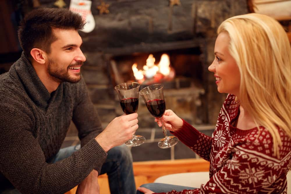 un couple amoureux assis devant une cheminée et griller du vin