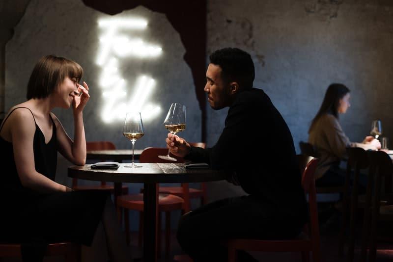 un couple amoureux boit du vin blanc et parle