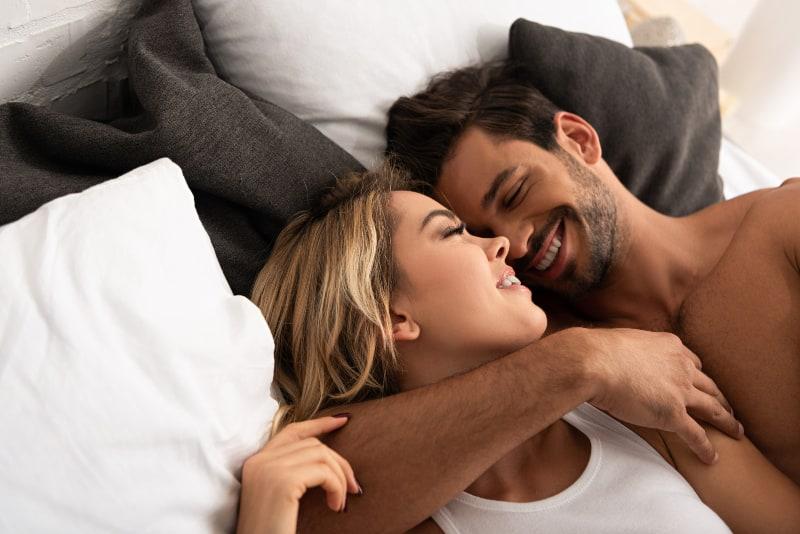 un couple souriant étreindre dans son lit le matin