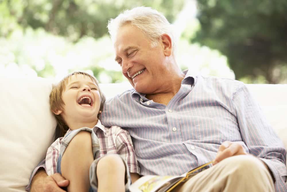 un grand-père et un petit-fils souriants sont assis dans un fauteuil