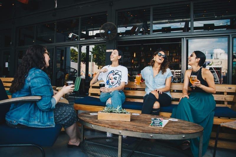 un groupe de femmes sur la terrasse d'un café buvant et parlant