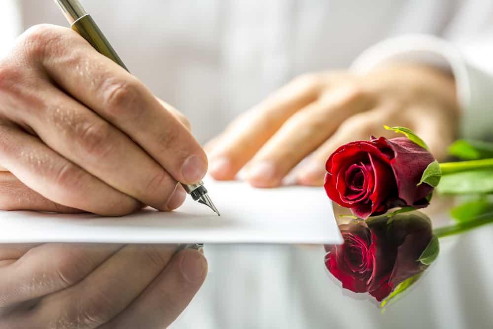 un homme écrit une lettre d'amour à côté de laquelle se trouve une rose rouge