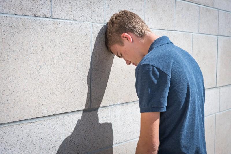 un homme appuyé contre un mur