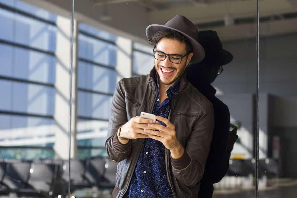 un homme avec un chapeau et des lunettes sur la tête écrit des sms