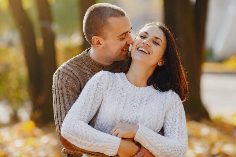 un homme avec une femme dans ses bras en riant