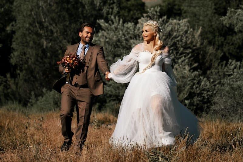 un homme avec une femme tient la main et court alors qu'elle est en robe de mariée