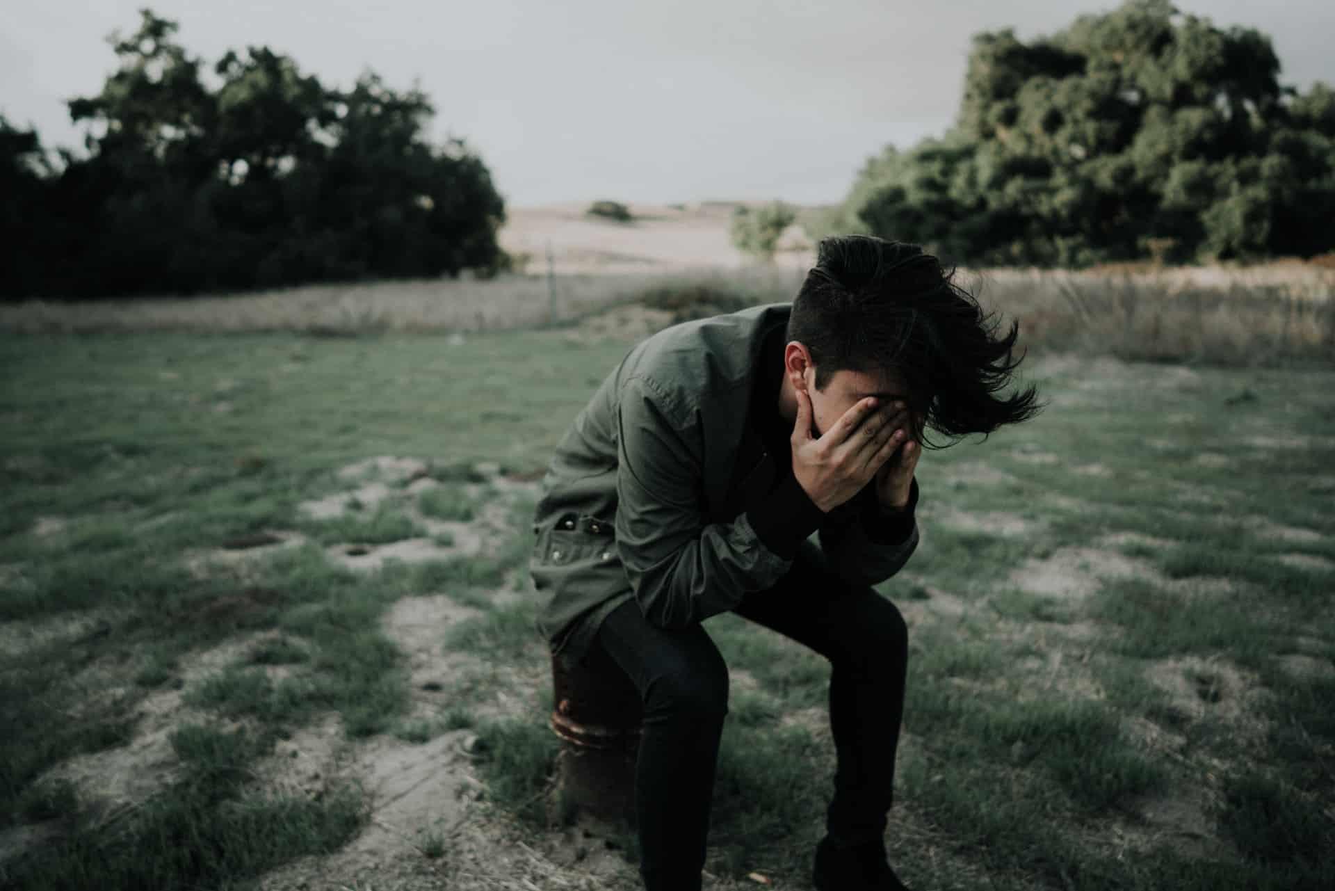 un homme déçu est assis dans un champ