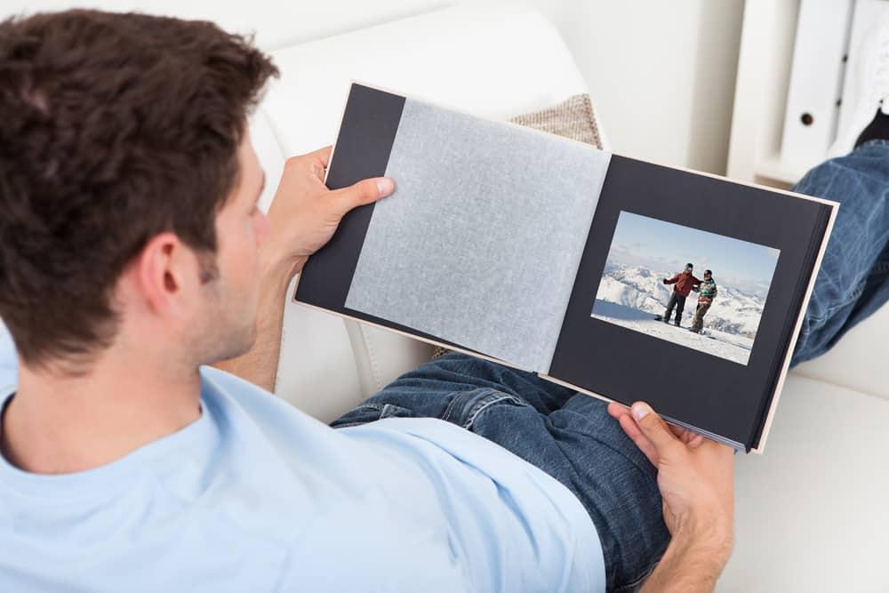 un homme est assis et regarde un album photo