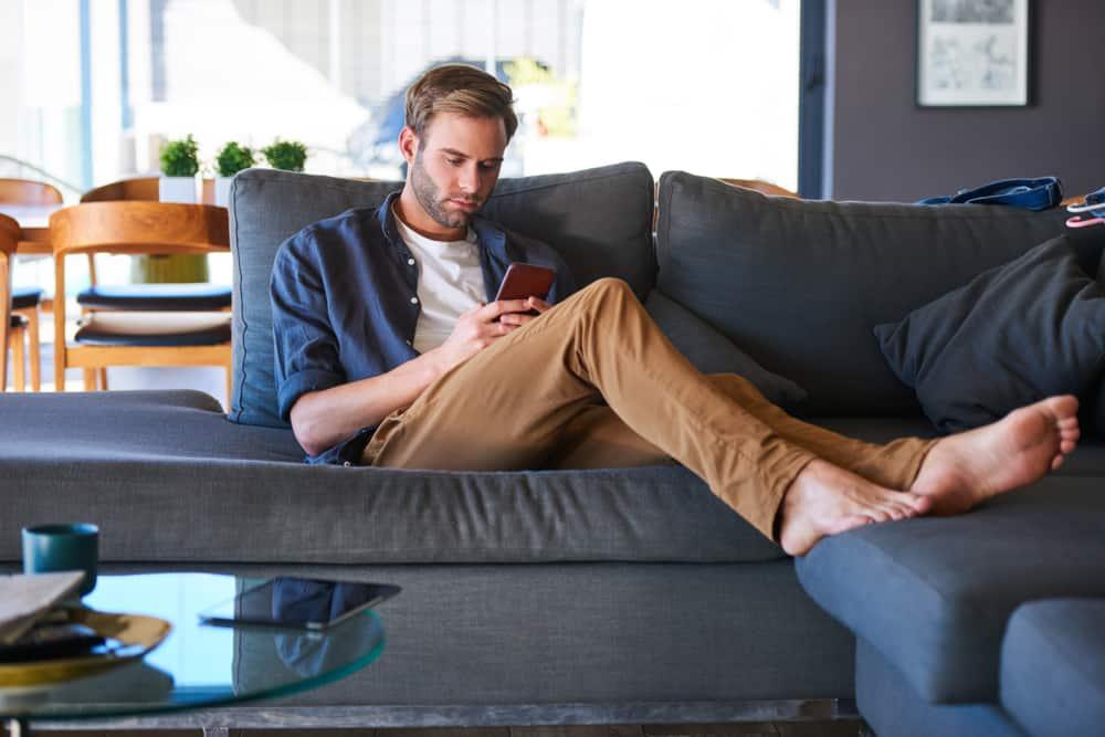un homme est assis sur un journal et écrit un sms
