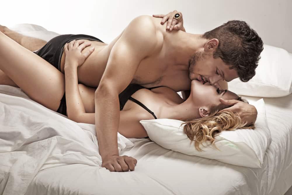 un homme et une femme à moitié nus au lit il l'embrasse