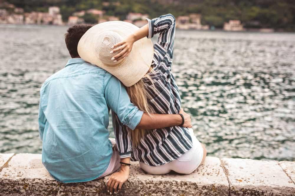 un homme et une femme assis embrassés par la mer