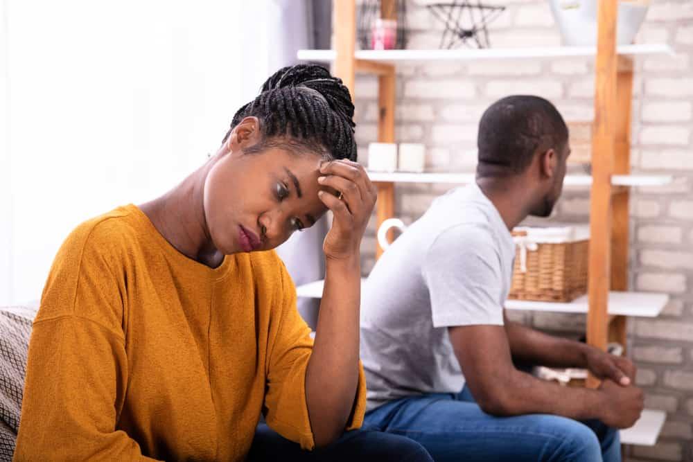 un homme et une femme assis sur le canapé en colère l'un contre l'autre